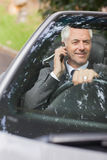 Smiling businessman on the phone driving expensive cabriolet Royalty Free Stock Images