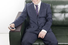 Smiling businessman with phone in hand in the office space. Young smiling man in a suit sitting on the couch and holding the phone in his hand Stock Images