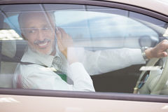 Smiling businessman on the phone in his car Royalty Free Stock Image