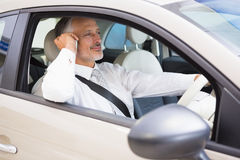 Smiling businessman on the phone in his car Royalty Free Stock Photo
