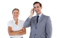 Smiling businessman on the phone next to his colleague Stock Photo