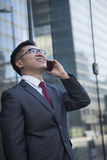 Smiling businessman on the phone outside in Beijing looking up Stock Photos