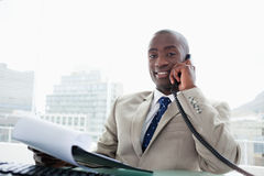 Smiling businessman on the phone while reading a document Royalty Free Stock Images