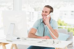 Smiling businessman on the phone while using computer Stock Photos