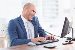 Smiling businessman on the phone and using his computer Stock Photos