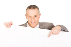 Smiling businessman pointing on empty banner Stock Photos