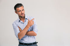 Smiling businessman pointing finger away stock photography