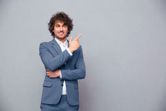 Smiling businessman pointing finger away Stock Images