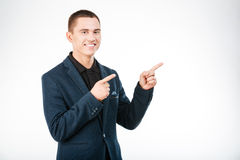 Smiling businessman pointing finger away Stock Photo