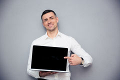 Smiling businessman pointing finger on blank laptop screen. Over gray background. Looking at camera Stock Photography