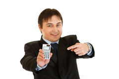 Smiling businessman pointing finger on calculator Royalty Free Stock Images
