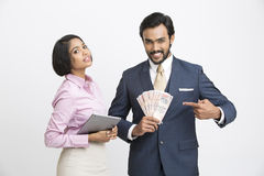Smiling businessman pointing money with his colleague. Happy smiling businessman holding money with his colleague on white background Royalty Free Stock Photo