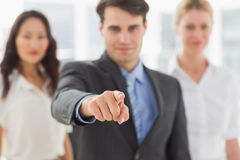 Smiling businessman pointing to camera in front of his team Royalty Free Stock Photo