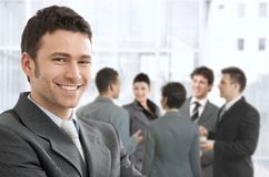 Smiling businessman portrait. Smiling confident businessman portrait, group of businesspeople chatting in background Stock Images