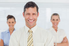 Smiling businessman posing with his colleagues on background Royalty Free Stock Images