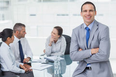 Smiling businessman posing while workmates talking together Stock Photo