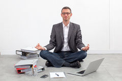 Smiling businessman practicing yoga at office for relaxation Stock Image