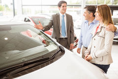 Smiling businessman presenting a car Royalty Free Stock Photos