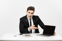 Smiling businessman presenting his laptop computer to the viewer with a blank screen with copy space.  Stock Photos