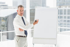 Smiling businessman presenting at whiteboard with marker Stock Photography