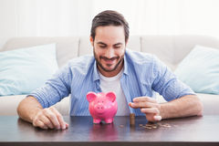 Smiling businessman putting coins into piggy bank Royalty Free Stock Photography