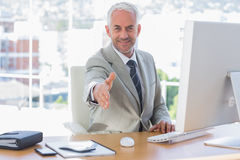 Smiling businessman reaching out arm for handshake Stock Image