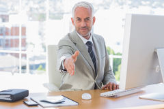 Smiling businessman reaching out hand for handshake Royalty Free Stock Image