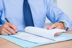 Smiling businessman reading a contrat before signing it Royalty Free Stock Photography