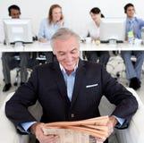 Smiling businessman reading a newspaper Stock Photos