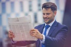 Smiling businessman reading newspaper Stock Photos