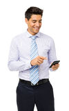 Smiling Businessman Reading Text Message On Smart Phone Royalty Free Stock Image