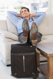 Smiling businessman relaxing on couch with feet up on suitcase Royalty Free Stock Image