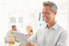 Smiling businessman scrolling on a tablet Stock Images