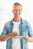 Smiling businessman scrolling on a tablet Stock Photos