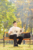 Smiling businessman seated on a bench reading a newspaper in a p Royalty Free Stock Images