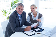 Smiling businessman with secretary checking file Stock Image