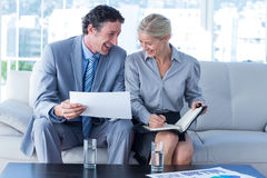 Smiling businessman and secretary looking at diary Royalty Free Stock Photos