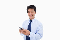 Smiling businessman sending a text message Stock Image