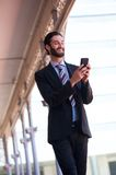 Smiling businessman sending text message on cell phone Stock Image