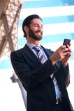 Smiling businessman sending text message on mobile phone Stock Photography