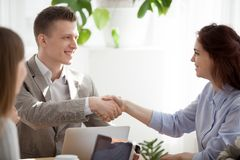 Diverse colleagues handshake getting acquainted at office meetin. Smiling businessman shake hand of young female colleague getting acquainted at workplace royalty free stock photography