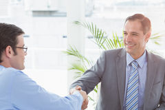 Smiling businessman shaking hands with a co worker Stock Images