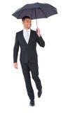 Smiling businessman sheltering under black umbrella Stock Images