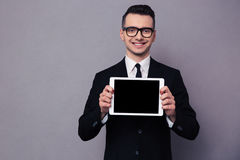 Smiling businessman showing blank tablet computer screen Stock Images