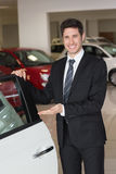 Smiling businessman showing a car for sale Royalty Free Stock Photo