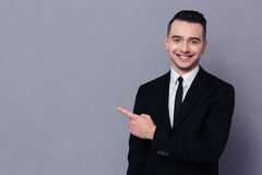 Smiling businessman showing finger away Stock Photos