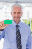 Smiling businessman showing green business card Royalty Free Stock Images
