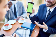 Smiling Businessman Showing Mobile Application on Phone. Closeup portrait of smiling businessman presenting smartphone with green blank screen to colleagues Royalty Free Stock Photography