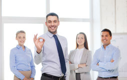 Smiling businessman showing ok-sign in office. Office, business, and teamwork concept - friendly young smiling businessman with team on back showing ok-sign Stock Photos
