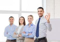 Smiling businessman showing ok-sign in office. Office, business, and teamwork concept - friendly young smiling businessman with team on back showing ok-sign Royalty Free Stock Photo